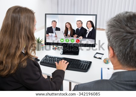 Two Businesspeople Video Chatting With Colleagues On Computer In Office #342196085