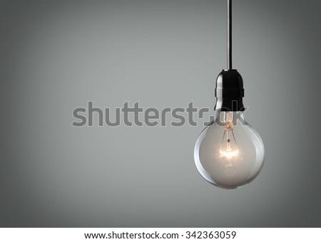 Vintage hanging light bulb over gray background  #342363059