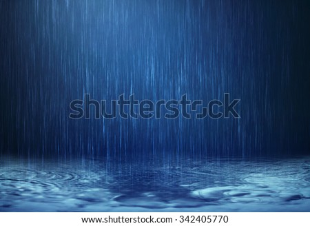 The rain water drop falling to the dark surface water on the floor in rainy season
