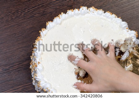 Hand tearing a large white cake #342420806