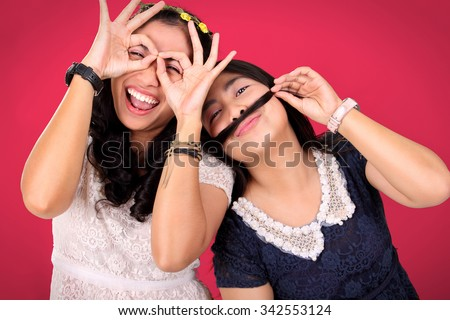 Two happy female best friends posing to camera with crazy gleeful expressions, over hot pink background