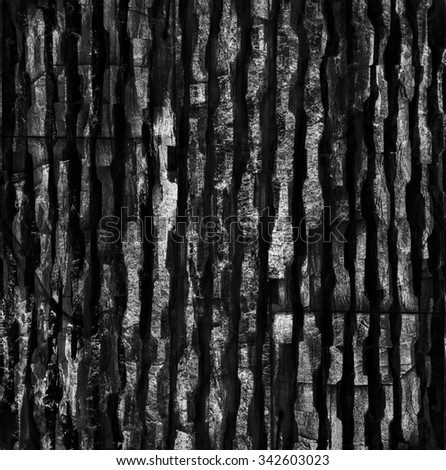 Hewn stone structure, or abstract black and white textured background. Rough uneven  pattern with sharp edges and comparatively wide and deep fissures / cracks between them forms dramatic composition. #342603023