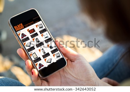 close-up view of young woman shopping on black friday with her mobile phone. All screen graphics are made up. #342643052