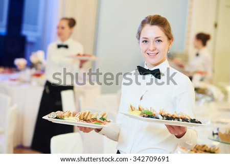 waitress occupation. Young woman with food on dishes servicing in restaurant during catering the event Royalty-Free Stock Photo #342709691