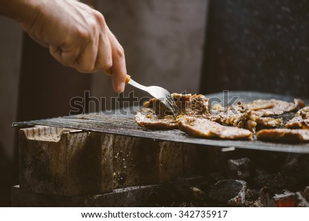 Unhealthy eating, man grilling pork meat chops on barbecue, natural light, retro toned, selective focus with shallow depth of field. #342735917