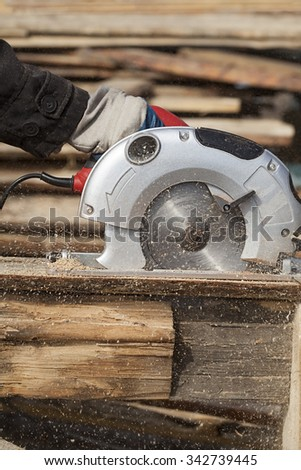 a man works outdoors with a circular saw #342739445