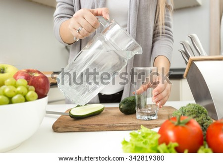Closeup photo of woman pouring water in glass on kitchen #342819380