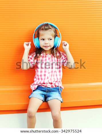 Beautiful smiling child listens to music in headphones over colorful orange background #342975524