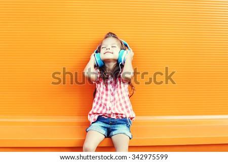 Happy smiling child enjoys listens to music in headphones over orange background #342975599