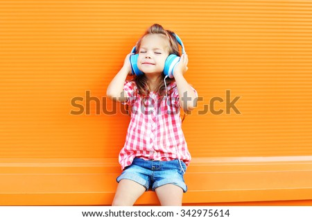 Happy smiling child enjoys listens to music in headphones over colorful orange background #342975614