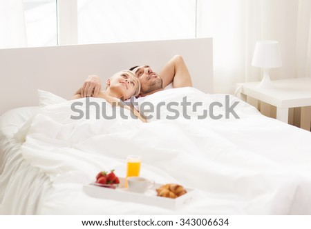 people, love, care and happiness concept - happy couple lying in bed with tray of breakfast at home #343006634