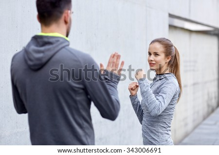 fitness, sport, martial arts, self-defense and people concept - happy woman with personal trainer working out strike outdoors Royalty-Free Stock Photo #343006691