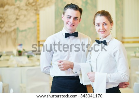 waiter and waitress occupation. Young man and woman at catering service in restaurant during event Royalty-Free Stock Photo #343041170