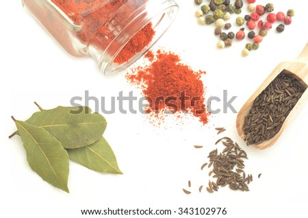 Red pepper in glass bottle, colorful pepper, bay leaves and cumin in wooden spoon isolated on white background #343102976