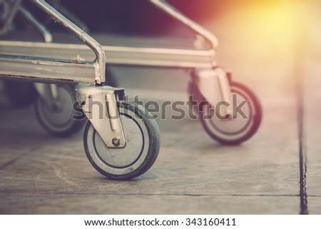 Shopping  cart wheel close up. Vintage filter. #343160411