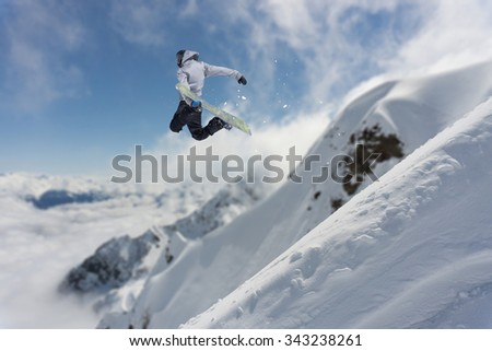 Flying snowboarder on mountains. Extreme winter sport #343238261