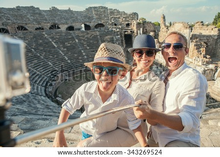 Young positive family take a vacation photo on the Side amphitheater  view