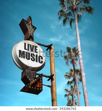 aged and worn vintage photo of live music sign with palm trees