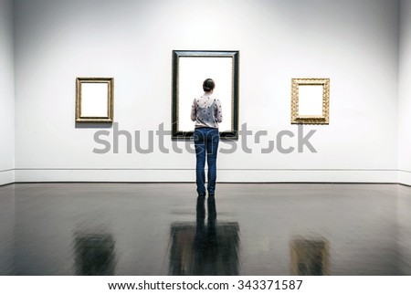 A woman is standing and looking at blank painting frames in art gallery. #343371587