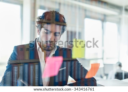 Shot through glass windows.Portrait of a stylish executive standing in a luminous office. He is looking at some folders, wearing a suit and beard. The reflection of the archives is on the window #343416761