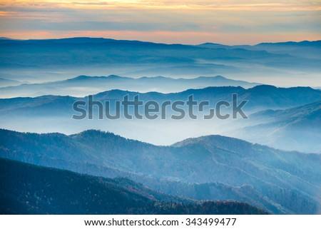 Blue mountains and hills under beautiful orange sunset #343499477