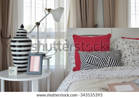 stylish bedroom interior with flower pattern pillows and decorative table lamp #343535393