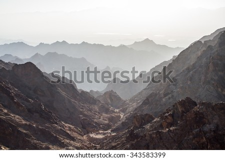 Early morning in ancient mountains of Sinai desert. Sunrise over Red sea #343583399