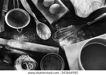 A set of old kitchen items close-up view from above. Kitchen table in a rustic style. Products for baking flour, eggs, salt. Black and white photo