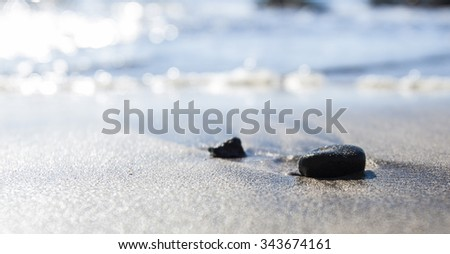 rock on the sand beach and the blue sea in background #343674161