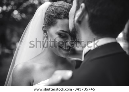 beautiful bride caress gently, the groom's face in the park #343705745
