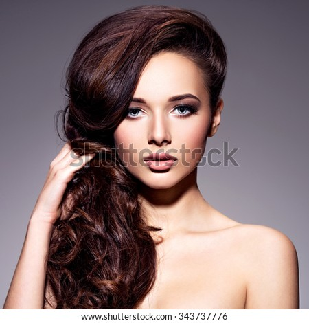 Portrait of the beautiful  young woman with long brown  hair posing at studio over dark background #343737776