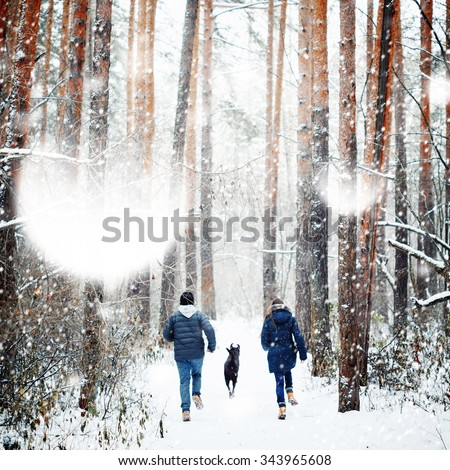 Young Family Having Fun with a Dog in Winter Forest on Vacations. Copy Space for Text. Selective Focus.