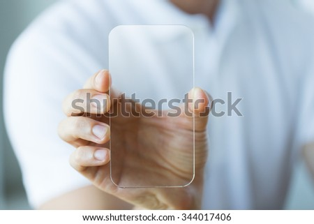business, technology and people concept - close up of male hand holding and showing transparent smartphone at office Royalty-Free Stock Photo #344017406