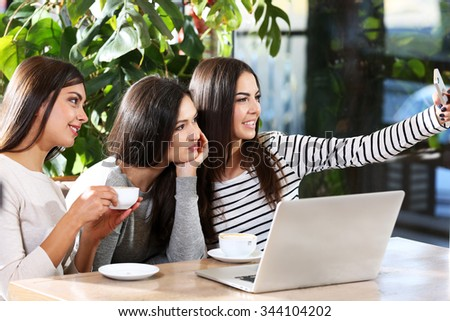 Best friends with laptop together takes selfie sitting in cafe #344104202