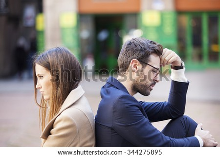 Bad relationship concept. Man and woman in disagreement. Young couple after quarrel sitting back to back. Outdoor  Royalty-Free Stock Photo #344275895