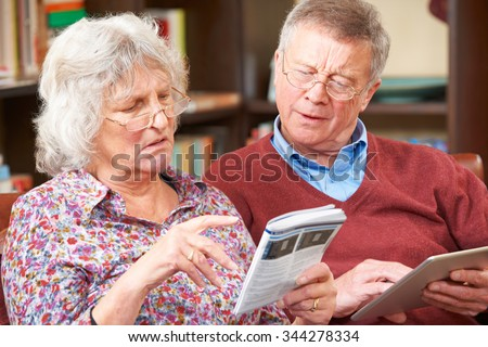 Confused Senior Couple Trying To Operate Digital Tablet #344278334