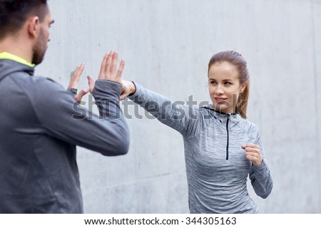 fitness, sport, martial arts, self-defense and people concept - happy woman with personal trainer working out strike outdoors Royalty-Free Stock Photo #344305163