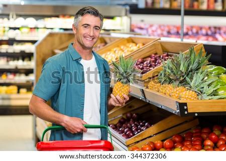 Smiling man choosing pineapple at supermarket #344372306