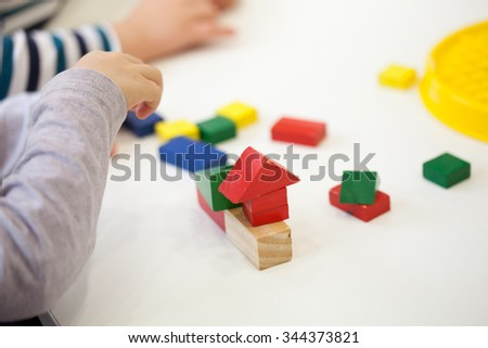 Child play with colored wooden brick shapes on white table. Close up view from above on hands and toys. #344373821