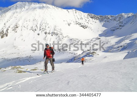 Team of ski mountaineers follow a snow trail in sunny winter day #344405477