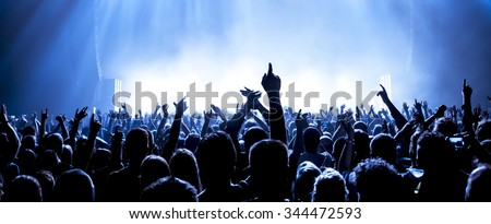 silhouettes of concert crowd in front of bright stage lights #344472593