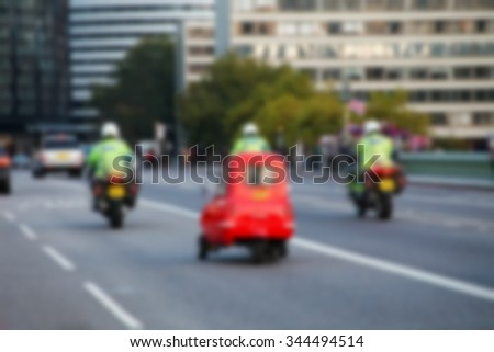 The blurry photo of metropolitan police of london riding on motorcycle leading the red car represent the people and transportation concept related idea. #344494514