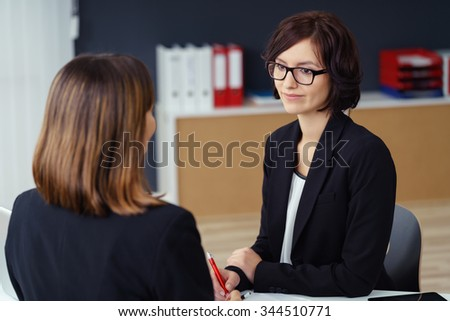 Pretty Young Businesswoman Listening to her Female Colleague Talking to her at her Table Inside the Office. Royalty-Free Stock Photo #344510771