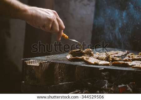 Barbecue time, man grilling pork meat chops, natural light, retro toned, selective focus with shallow depth of field. #344529506
