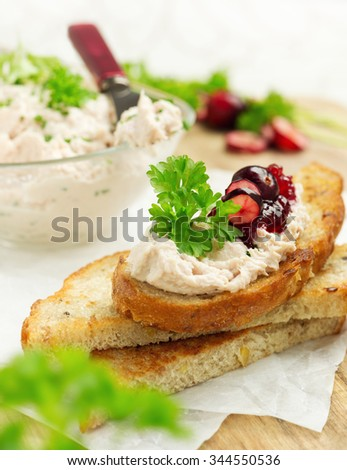 Crispy multigrain toasts with chicken cream, cranberry jam and parsley #344550536