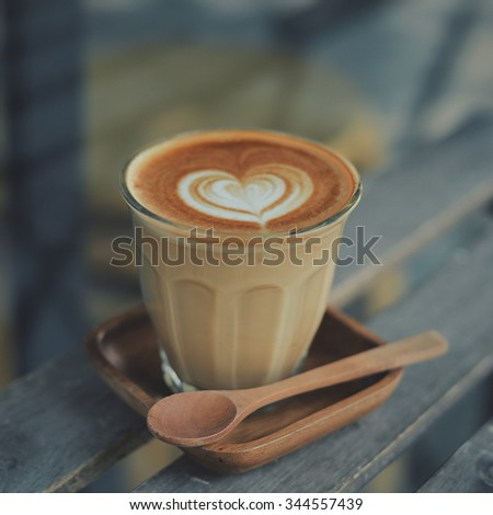 cup of coffee latte on the wood texture   in vintage color tone #344557439