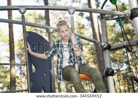 Portrait of happy smiling adolescent caucasian boy in having fun at a summer playground. #344569412