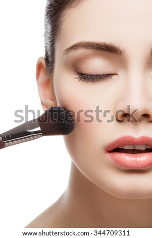 Beautiful young woman applying blush with brush. Isolated over white background. Copy space. #344709311