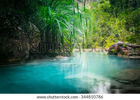 Jungle landscape with flowing turquoise water of Erawan cascade waterfall at deep tropical rain forest. National Park Kanchanaburi, Thailand #344810786