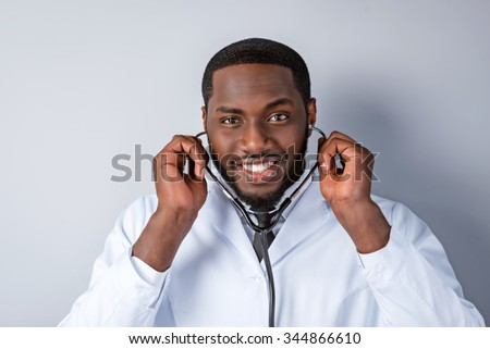 Portrait of male afro american doctor with stethoscope and lab coat. Young doctor smiling and looking at camera. Man standing on grey background #344866610